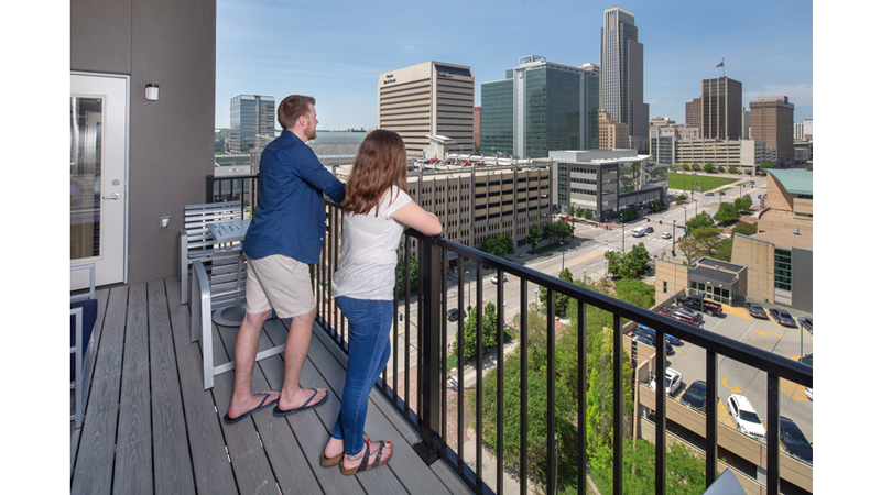 Couple on balcony at Capitol District apartments with views of downtown Omaha.